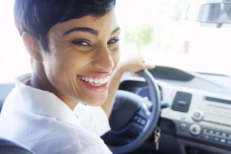 happy woman driving away after getting her title loan scaled e1579557500701