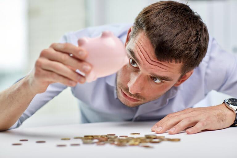 man looking at empyt piggy bank