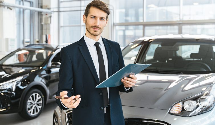 man holding a chart in front of a car